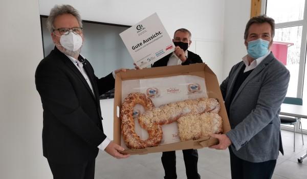 Vorstände Wolfgang Sartorius (li.)  und Bernd Messinger (re.) übergeben mit einem symbolischen Schlüssel den Neubau an den Leiter der Sozialtherapie Klaus Engler (Bildmitte).