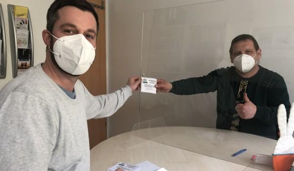 Sozialarbeiter Swen Schreier (li.) übergibt einen Essensgutschein im Rahmen seiner Sozialberatung.